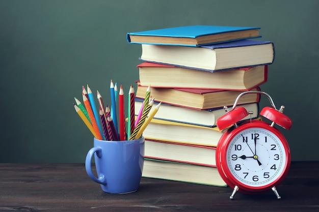 Une pile de livres, des crayons et un réveil rouge sur la table.