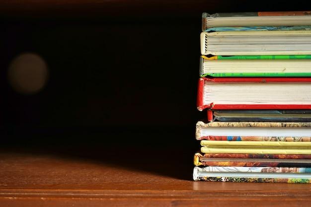 Pile de livres dans une armoire en bois avec fond sombre espace vide