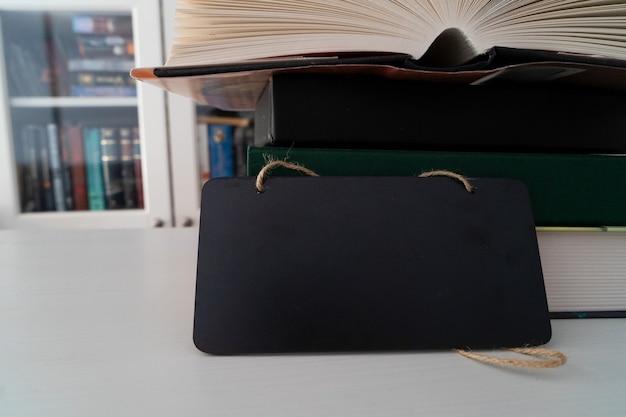 Pile de livres dans la bibliothèque avec des étagères à livres en arrière-plan, espace de copie sur ardoise noire