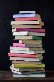 Pile de livres dans la couverture colorée sur la table à l'arrière-plan d'un tableau d'école.