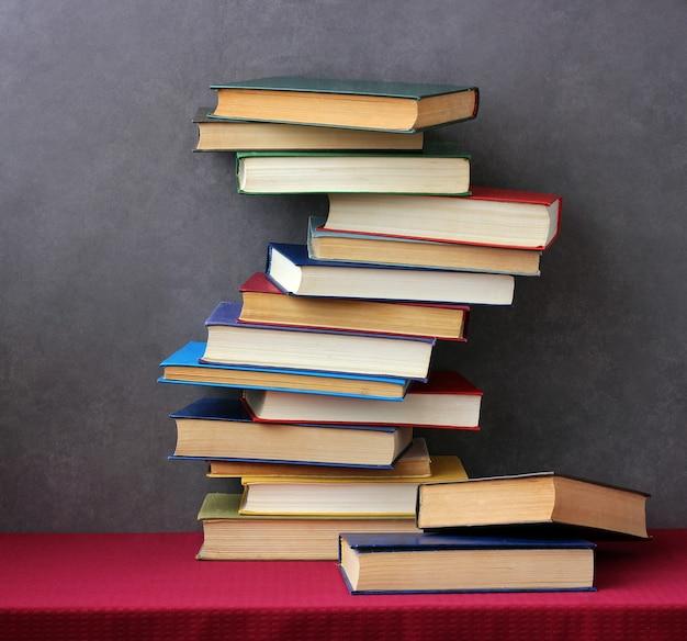 Une pile de livres dans les couvertures colorées sur la table avec une nappe rouge. nature morte avec des livres.