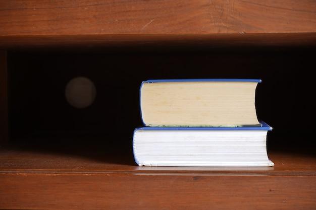Pile de livres dans une étagère d'armoire marron foncé pour le fond de l'éducation