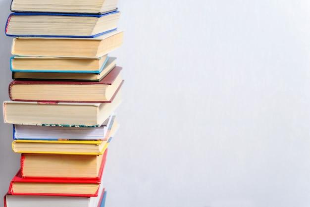 Pile de livres différents sur une table sur un fond de mur blanc