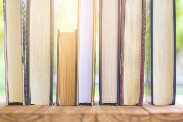 Pile de livres épais avec belle lumière et fond bokeh.