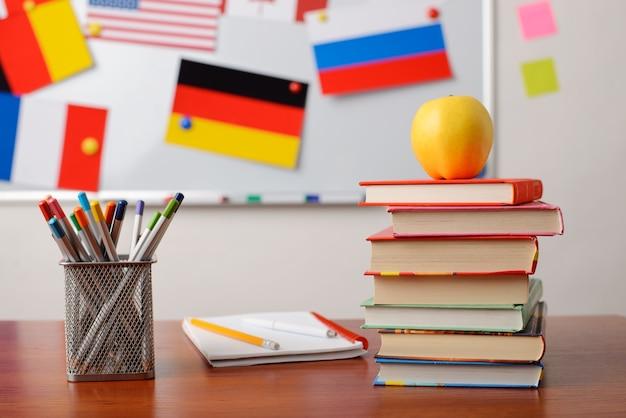 Pile de livres d'exercices sur table avec une planche pleine de drapeaux différents sur l'arrière-plan