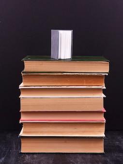 Pile de livres sur fond noir avec un petit livre sur le dessus