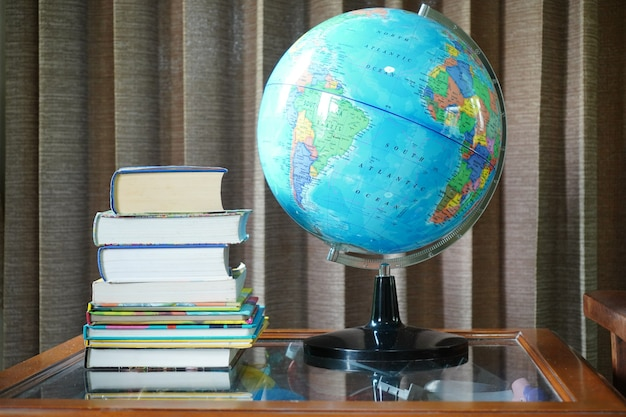 Pile de livres et globe simulé sur table en arrière-plan rideau soufflé