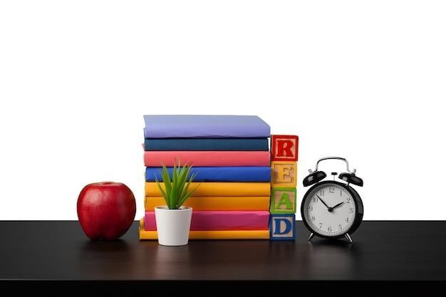 Pile de livres et heure de réveil pour lire le concept