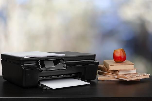 Pile de livres et imprimante à domicile sur fond flou
