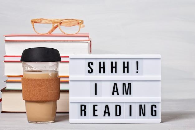 Pile de livres, lightbox avec le texte, tasse de café