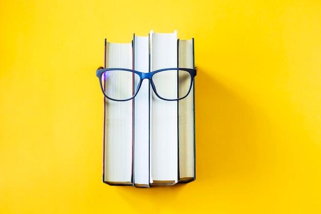 Une pile de livres avec des lunettes est une image du visage d'une personne