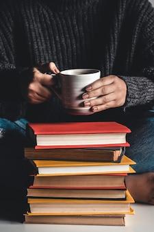 Pile de livres avec mug sur le dessus devant un livre de lecture de femme