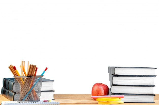 Pile de livres avec notes papier et stylo, pomme et crayons dans le conteneur de panier sur la table en bois