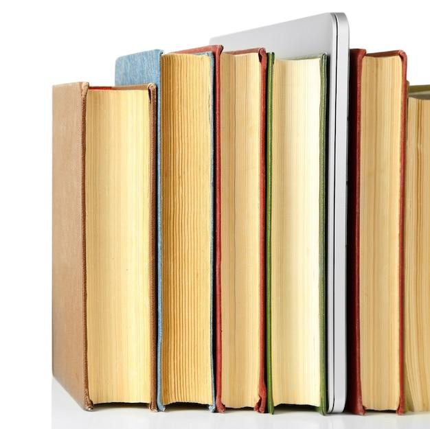Pile de livres avec ordinateur portable isolé sur blanc
