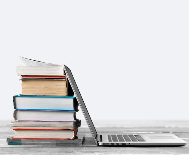 Pile de livres avec ordinateur portable sur table
