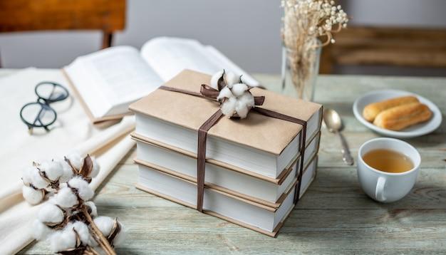 Une pile de livres en papier craft joliment emballés attachés avec un ruban et décorés de coton sur une table en bois