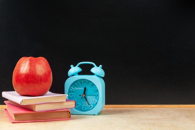 Pile de livres avec pomme et crayon sur table