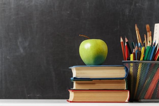 Une pile de livres, une pomme, des crayons au tableau.