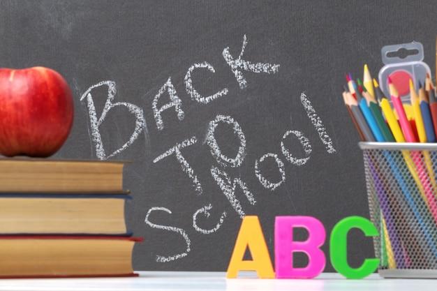 Une pile de livres, une pomme, des lettres de l'alphabet, des crayons. retour à l'école