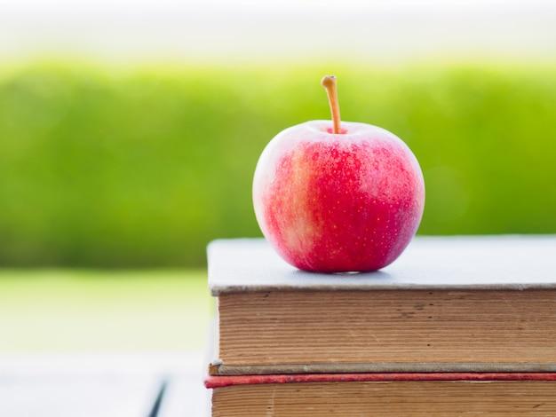 Pile de livres et pomme rouge sur une table en bois.