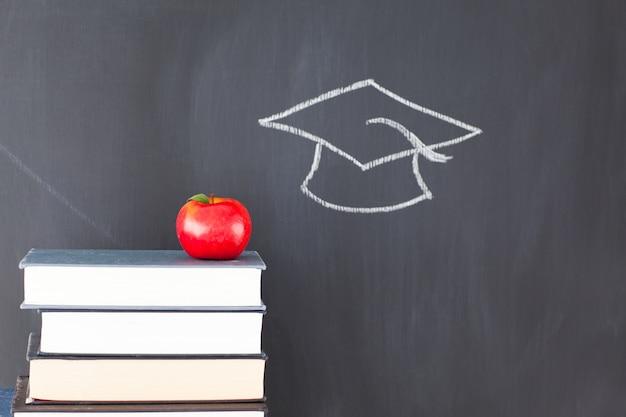 Pile de livres avec une pomme rouge et un tableau noir avec un chapeau de graduation dessiné dessus