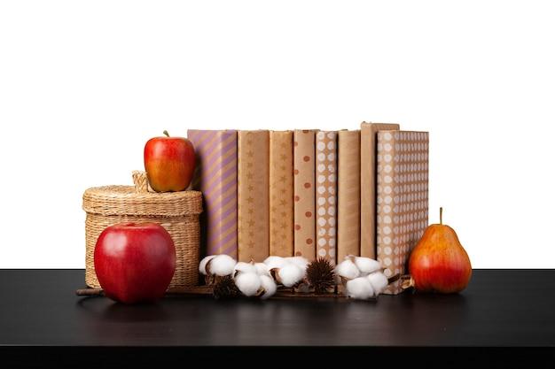 Pile de livres et pomme sur table contre fond blanc