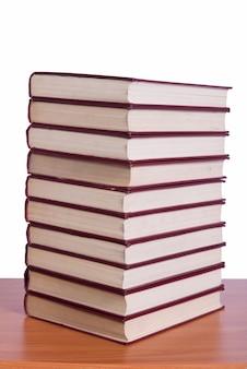 Une pile de livres rangée sur le bureau