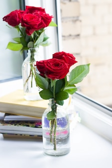 Pile de livres et de roses dans des vases près d'une fenêtre ouverte