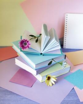 Pile de livres avec des signets de papier coloré de fleurs sur la table