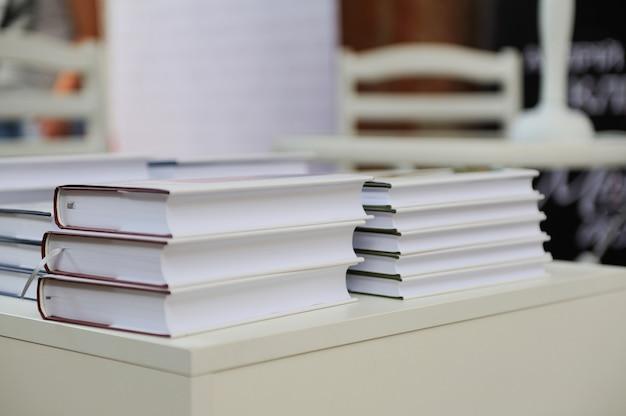 Une pile de livres sur une table blanche