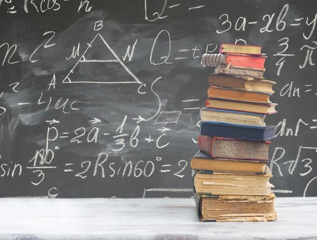 Pile de livres sur table en bois blanc avec des formules mathématiques sur tableau noir