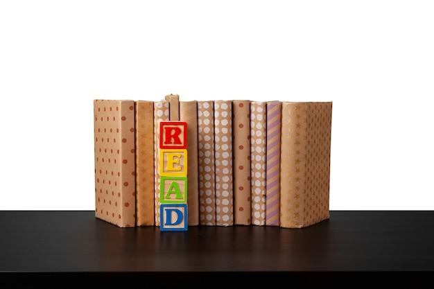 Pile de livres sur table en bois contre fond blanc