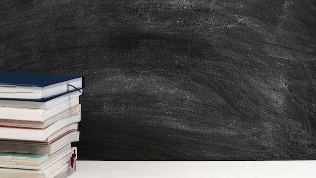 Pile de livres sur le tableau de l'école avec des stylos et des crayons