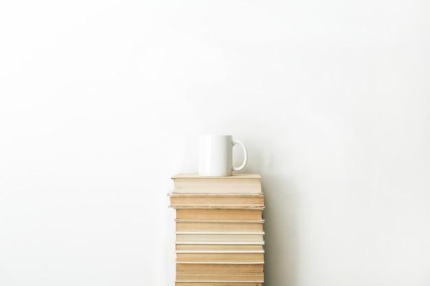 Pile de livres et tasse de café sur une surface blanche