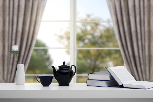 Une pile de livres et de thé frais sur une table blanche dans le contexte d'une fenêtre et d'un jardin arboré. concept d'apprentissage de l'éducation.