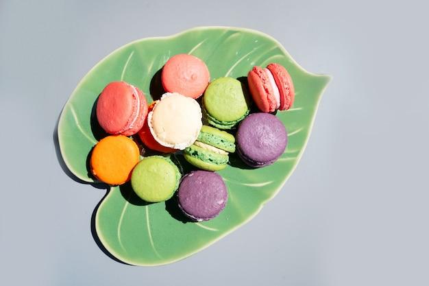 Pile de macarons de biscuits français sur plaque de feuilles sur fond gris, vue de dessus