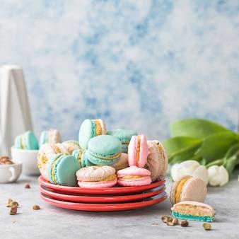 Pile de macarons français ou italiens colorés sur plaque rouge. dessert servi avec thé de l'après-midi ou pause café. beau fond de repas