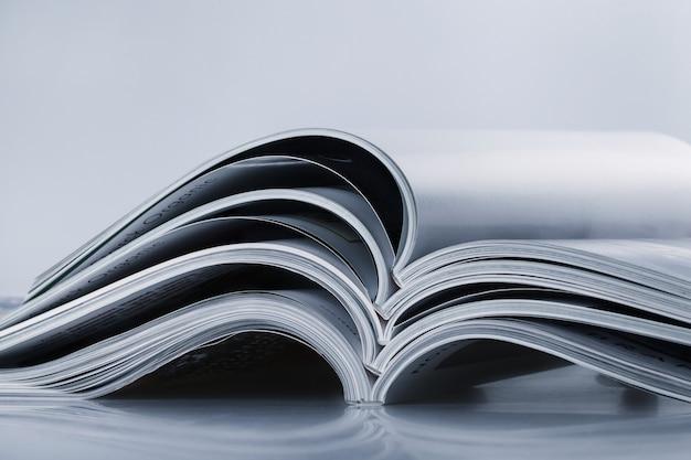 Pile de magazines ouverts, image aux tons bleus