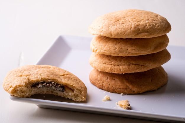 Pile maison de biscuits au chocolat sablés avec un cookie mordu sur table en bois plaque blanche
