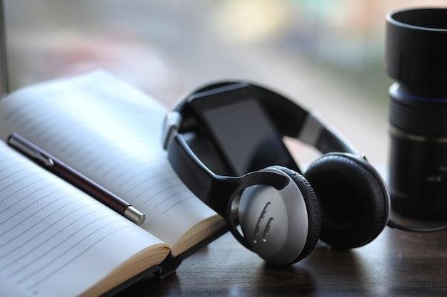 Une pile de manuels avec des écouteurs noirs sur une table