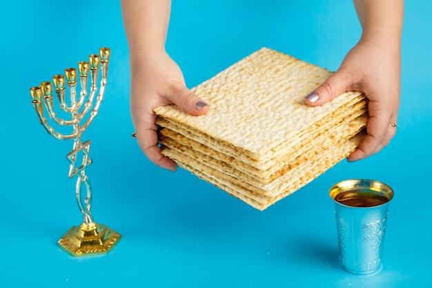 Une pile de matzo dans les mains des femmes sur une surface bleue à côté d'un verre de vin menorah