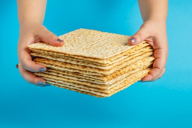 Pile de matzo dans les mains des femmes sur la surface bleue photo horizontale