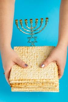 Une pile de matzo dans les mains des femmes sur une surface bleue près de la menorah