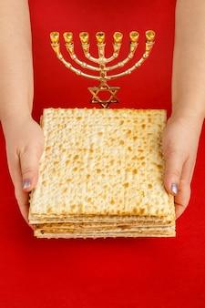 Une pile de matzo dans les mains des femmes sur une surface rouge près de la menorah
