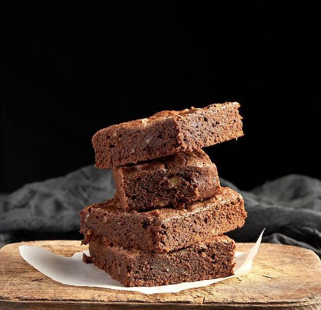 Pile de morceaux carrés au four de gâteau au chocolat brownie sur une planche à découper en bois marron