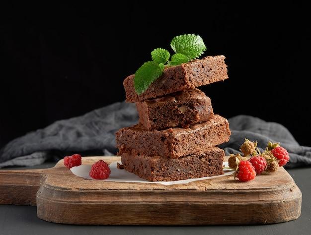 Pile de morceaux carrés cuits au four de gâteau au chocolat brownie sur une planche à découper