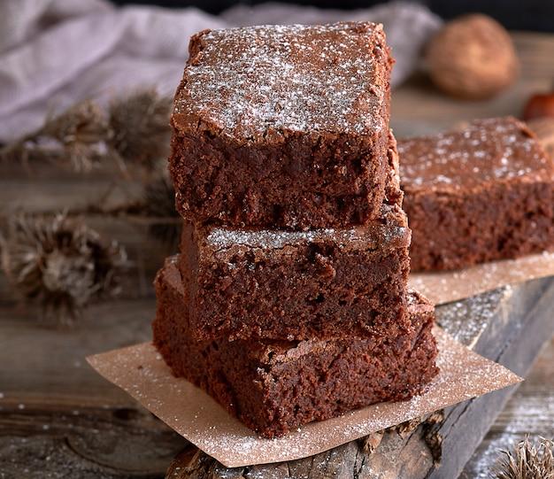 Pile de morceaux carrés cuits de tarte au brownie sur une planche de bois