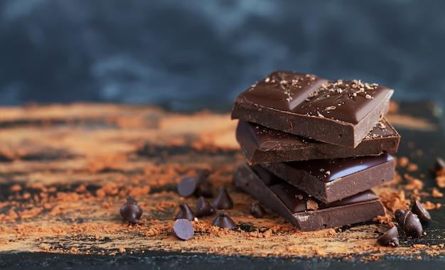 Pile de morceaux de chocolat avec des flocons de chocolat, des gouttes et du cacao en poudre sur une surface sombre