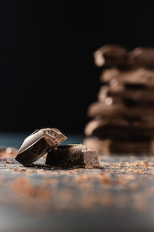 Pile de morceaux de chocolat noir sur noir. fermer. copiez l'espace.