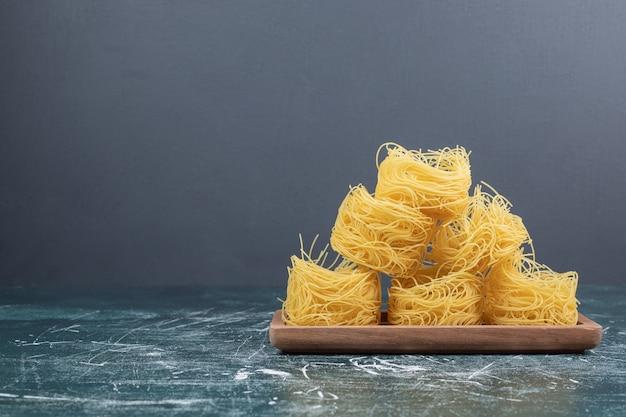 Pile de nids de spaghettis crus sur planche de bois. photo de haute qualité